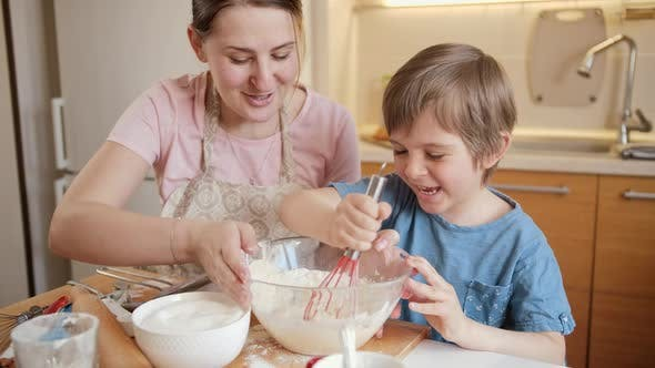 Happy Laughing Little Boy Mixing Dough Ingredients in Big Bowl