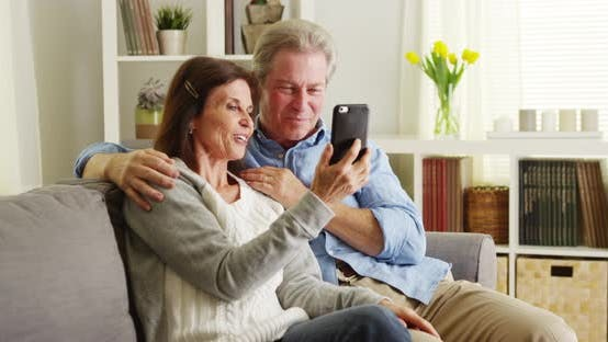 Thumbnail for Elderly couple using smartphone on couch
