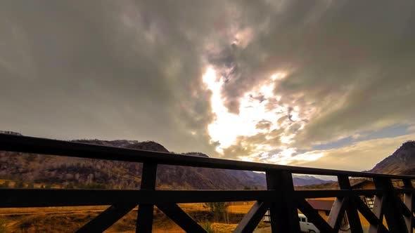 Thumbnail for Zeitraffer von Holzzaun auf Hochterrasse bei Berglandschaft mit Wolken