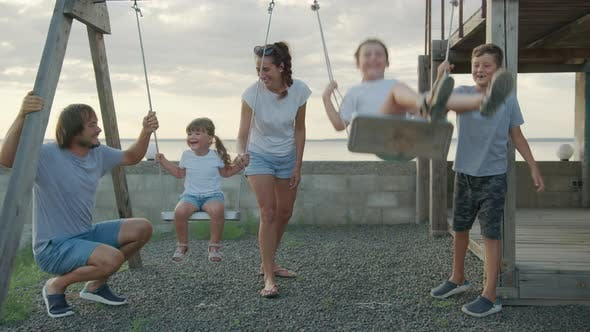 Thumbnail for Happy Family Rolls Young Children on a Swing Outdoors at Sunset.