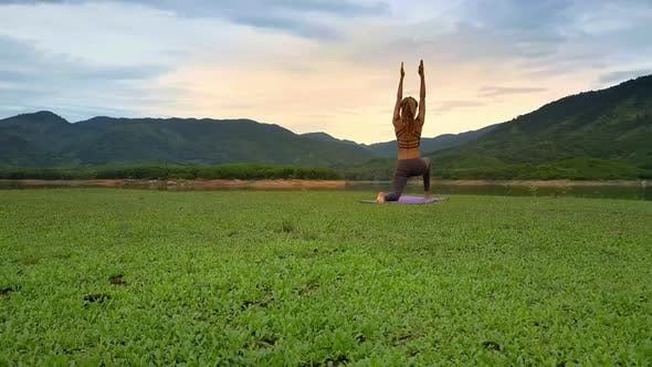 Thumbnail for Backside View Girl Stands in Yoga Pose with Hands Up at Lake
