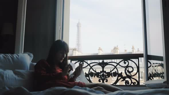 Thumbnail for Beautiful Happy Blogger Woman Lying on Bed at French Balcony Window with Eiffel Tower View Using