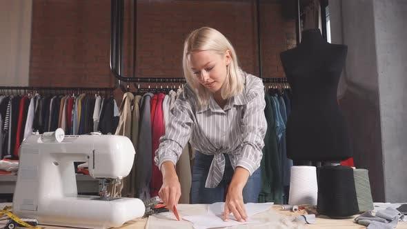 Cheerful Blonde Designer Making Up a Fashion Clothing