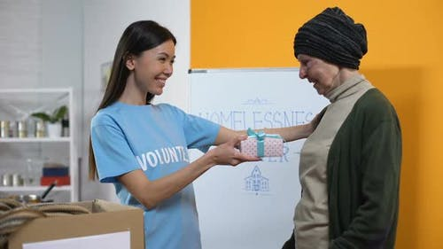 Smiling Volunteer Presenting Gift Box to Needy Aged Female, Philanthropy Care