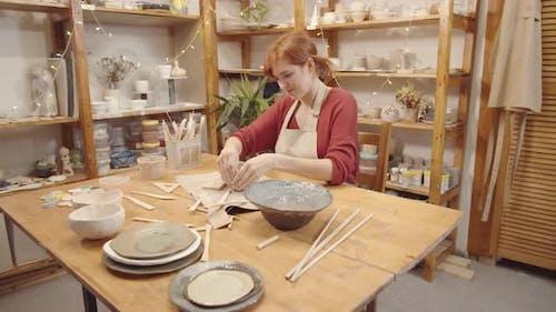 Happy Female Potter Making Handmade Earthenware Vessel in Workshop