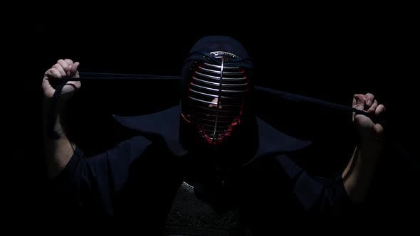 Cover Image for Kendo Warrior Is Putting on Helmet and Lacing It. Slow Motion. Close Up