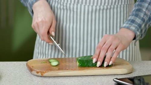 Female Hands Cutting Cucumber