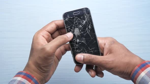 Close Up of Man Hand Holding Broken Smart Phone.