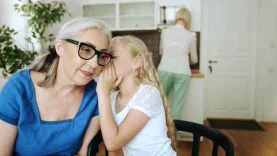 Granddaughter Whispering To Granny Indoors