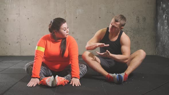 Thumbnail for Young Active Pleasant Personal Trainer Talking with His Client While Doing Sport
