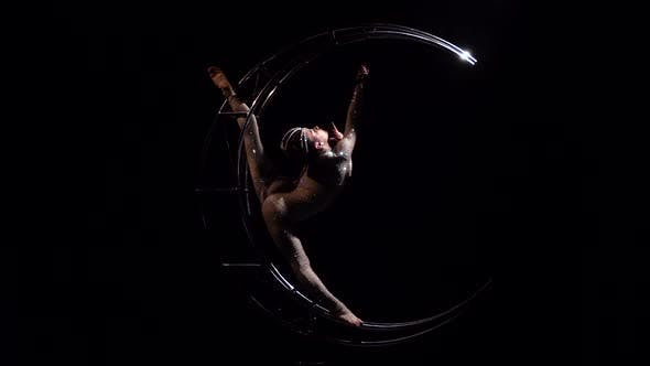 Thumbnail for Gymnast Rotates on a Metal Structure Moon in a Vertical String. Black Background
