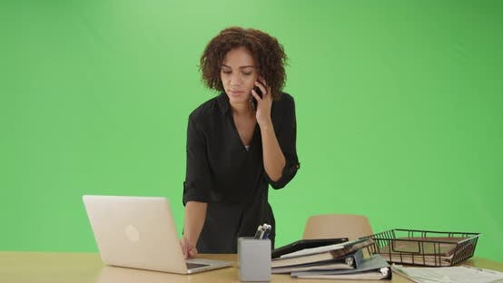 Thumbnail for Millennial black woman takes notes and listens to a phone call on green screen