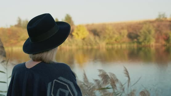 A Woman Looking at the Back of a Woman Admiring the Beautiful Lake