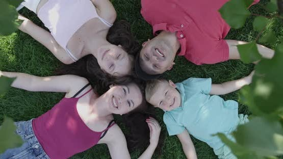 Happy Family Laying Down On A Green Grass And Looking Up Smiling In A Shade Of A Tree In The Summer