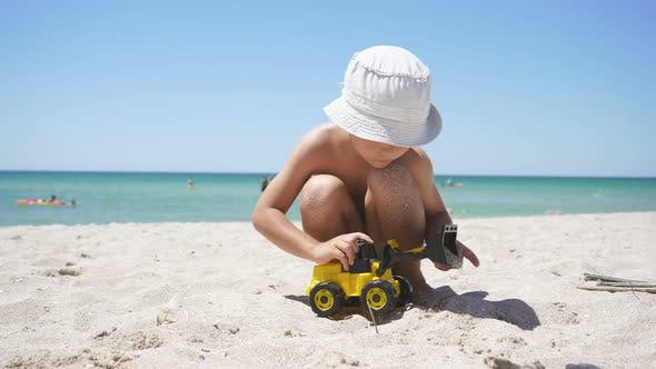 On a Sunny Summer Day, a Child Plays with a Toy Excavator on a Sandy Beach, with an Azure Sea