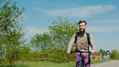 A Young Bearded Man is Riding a Bicycle