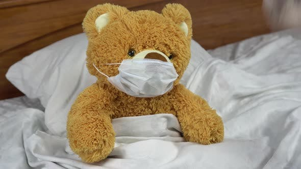A Teddy Bear Measures the Temperature with a Mercury Thermometer. The Doctor Puts a Thermometer To