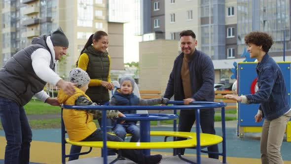 Cover Image for Happy Parents Spinning Roundabout for their Sons on Playground