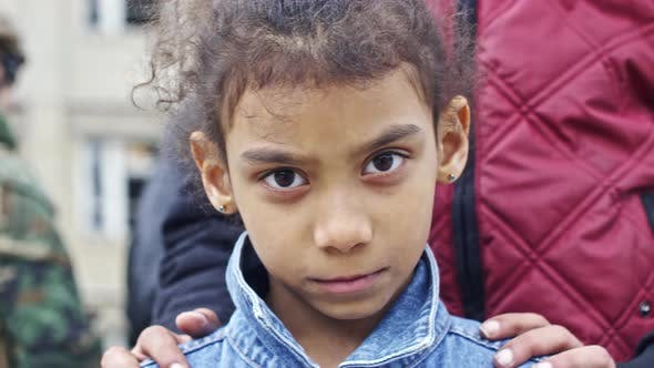 Cover Image for Little Refugee Girl Looking into Camera
