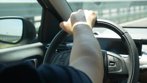 Driving pov of a hand on a steering wheel.