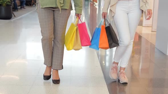 Female Shoppers Walk at Shopping Mall with Sale Bags in Slow Motion