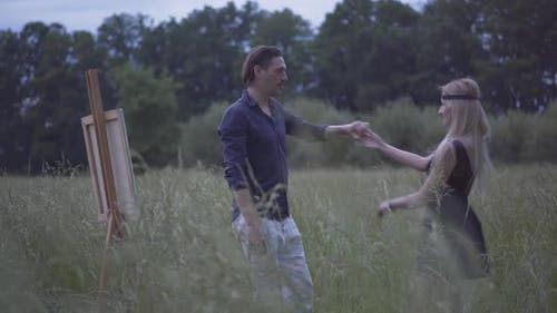 Happy Loving Man and Woman Dancing on Summer Meadow at Dusk. Portrait of Smiling Cheerful Caucasian