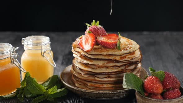 Honey Dripping Down on Pancake Stack. Slow Motion. Food Pancake Maple Syrup Pouring Onto Stack of