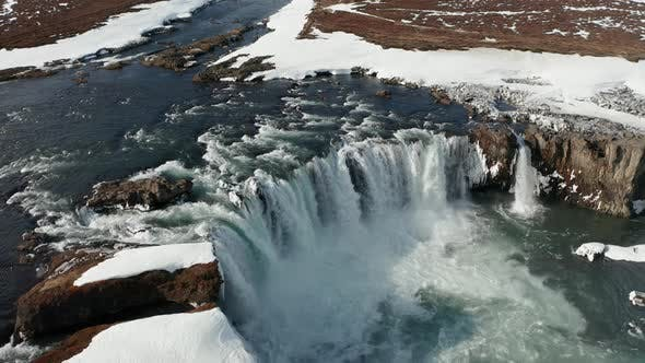 Thumbnail for Aerial View of Godafoss Waterfall with Snowy Shore and Ice, Iceland, Winter 2019