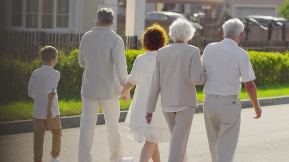 Thumbnail for Multigenerational Family Walking Together Outdoors on Sunny Day