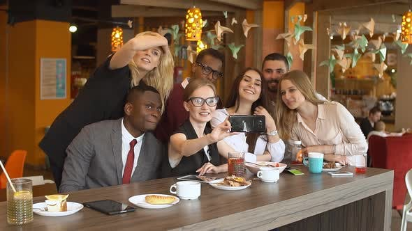 Thumbnail for Multinational Group of Friends in a Cafe Doing Selfie