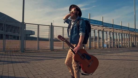 Hipster Bearded Male Musician with Dark Warm Eyes Walking in the Park on a Sunny Day with a Guitar