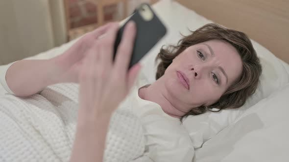 Thumbnail for Beautiful Old Woman Using Smartphone in Bed