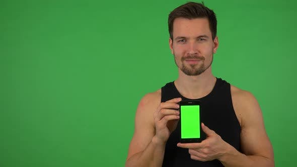 Thumbnail for A Young Handsome Athlete Shows a Smartphone with Green Screen To the Camera - Green Screen Studio