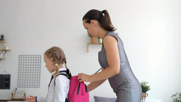 Mother Puts School Lunch in Backpack of Daughter