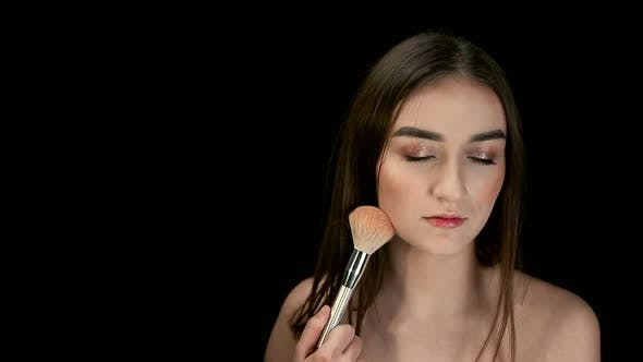 Thumbnail for Fashion Model Girl Holds a Powder Brush in Her Hand and Shakes Off the Powder. Small Particles of