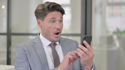 Middle Aged Man Celebrating on Smartphone