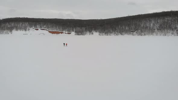 Thumbnail for Aerial Shooting of a Two Guys Trekking Crossing Frozen River