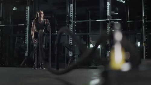 Young Woman Performs Exercises with Battle Ropes Endurance Training in the Gym  Slow Motion