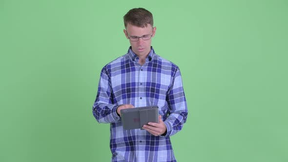 Thumbnail for Portrait of Happy Hipster Man Thinking While Using Digital Tablet