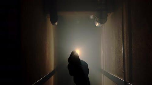 Boxer boxt mit einem Schatten in einem halbdunklen Korridor mit Hintergrundbeleuchtung hinter dem Rücken, Zeitlupe.
