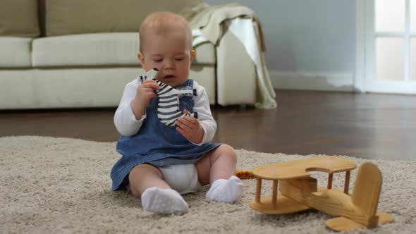 Caucasian Baby Girl Nibbling on Toy