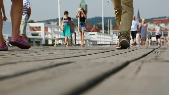 Thumbnail for Footsteps of people strolling along old wooden pier, enjoying beauty of sea