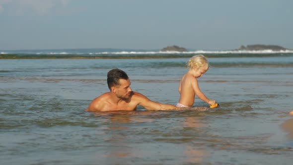 Thumbnail for Daughter Plays with Car Toy Swimming in Ocean Near Father