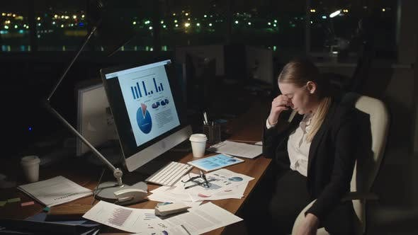 Cover Image for Tired Businesswoman Analyzing Stats at Night