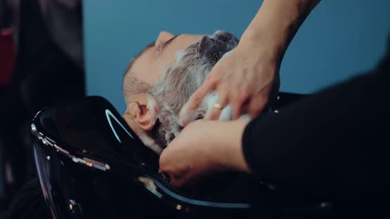 Hairdresser Shampooing Client's Hair a Lot of Foam on His Head
