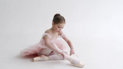 Little Girl in a White Tutu Sits on the Floor and Ties the Ribbons of Her Pointe Shoes Young