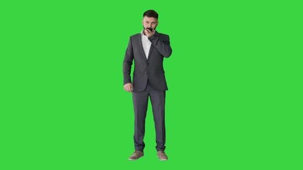 Geschäftsmann mit Speak aktivieren Virtual Digital Voice Assistant auf dem Smartphone auf einem grünen Bildschirm