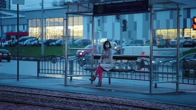 Lonely Woman at Tram Stop in the Evening