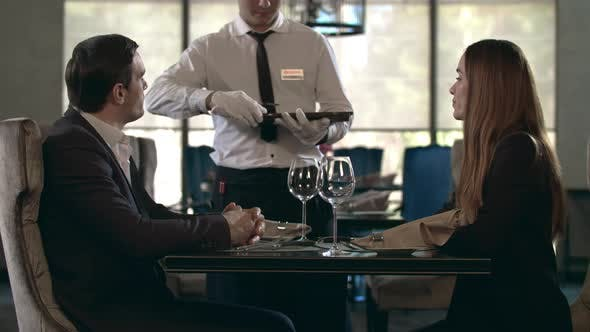 Thumbnail for Happy Couple Talking at Restaurant. Table. Business Couple Reading Menu in Cafe