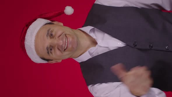 Vertical Shot Christmas Wreath Flies Into Frame and Falls on Neck Happy 40s Man in Santa Hat